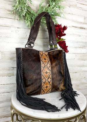 Coffee concealed carry large handbag with cowhide, fringe, and embossed Aztec print in the middle, with two braided shoulder straps, taken inside on white table with floral décor