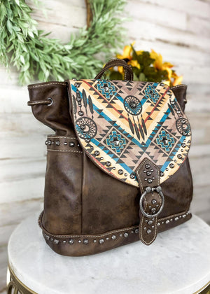 Coffee Colored Backpack with flap over closure with Dream Catcher Aztec Print, antique silver studs and two side pockets, taken inside on white table with floral décor