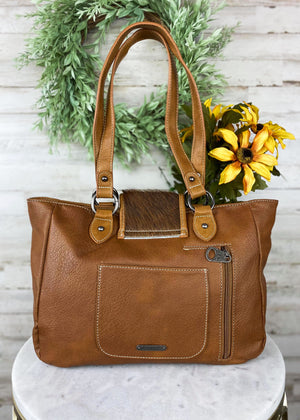 back of Brown Concealed Carry Handbag with Flap Over Snap Button Closure and Brown Cowhide and Fringe , with woven accents and 2 front zipper pockets and two shoulder straps, with silver hardware, taken inside on white table with floral décor