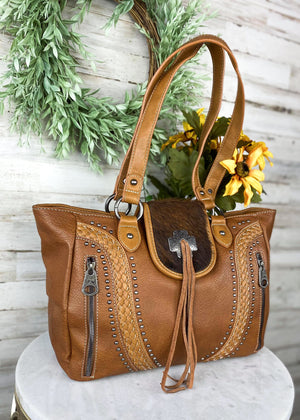 Brown Concealed Carry Handbag with Flap Over Snap Button Closure and Brown Cowhide and Fringe , with woven accents and 2 front zipper pockets and two shoulder straps, with silver hardware, taken inside on white table with floral décor