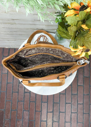 Inside of Brown Concealed Carry Handbag with Flap Over Snap Button Closure and Brown Cowhide and Fringe , with woven accents and 2 front zipper pockets and two shoulder straps, with silver hardware, taken inside on white table with floral décor
