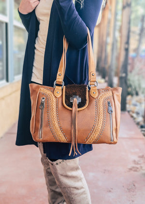 Brown Concealed Carry Handbag with Flap Over Snap Button Closure and Brown Cowhide and Fringe , with woven accents and 2 front zipper pockets and two shoulder straps, with silver hardware, taken outside on blonde model wearing navy cardigan and taupe knee high boots