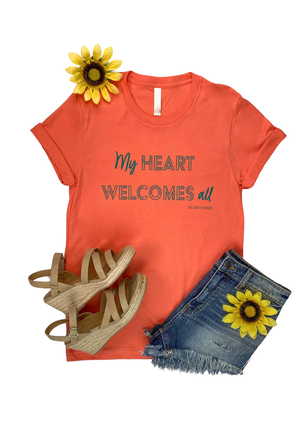 "Coral Short Sleeve Tee with "" My Heart Welcomes All"" in Teal Ink in the center"