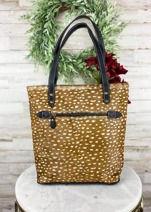 Medium sized tote handbag with brown hairon and deer spotted detail all over the bag, with black leather accents and straps, and back zipper pocket and 3 Inside pockets, taken inside on white table with floral décor