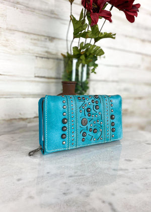 Turquoise tri wallet with gun metal hardware and concho studs, with zip around and snap button closure, taken on white table with floral décor