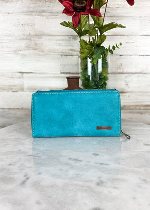 Back view of Turquoise tri wallet with gun metal hardware and concho studs, with zip around and snap button closure, taken on white table with floral décor