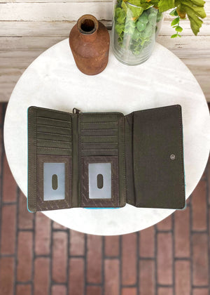 Inside view of Turquoise tri wallet with gun metal hardware and concho studs, with zip around and snap button closure, taken on white table with floral décor