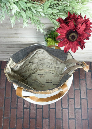 Medium sized tote handbag with brown floral print on the front and grey cowhide at the bottom, and grey canvas material, brown leather accents and shoulder straps, outside back zipper pocket and 3 inside pockets, taken inside on white table with floral décor