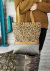 Medium sized tote handbag with brown floral print on the front and grey cowhide at the bottom, and grey canvas material, brown leather accents and shoulder straps, outside back zipper pocket and 3 inside pockets, taken inside on model