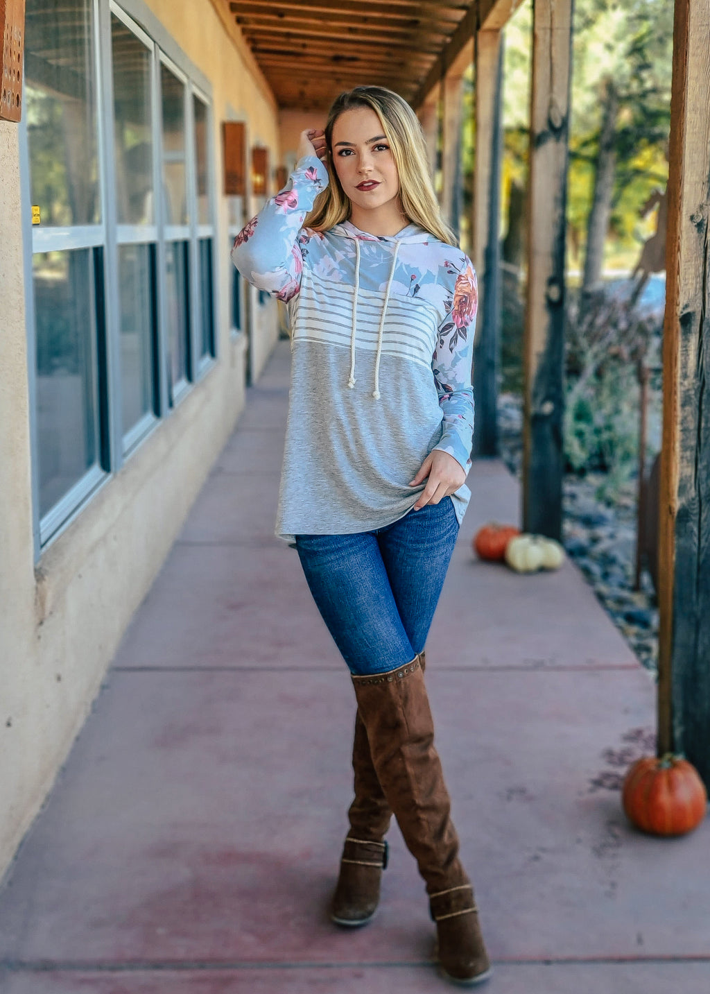 Grey Long Sleeved Hoodie with Ivory and Grey Stripes Block and Blue Floral Top Half, On Blonde Model with Denim Jeans and Brown Knee High Boots, Taken Outside in Natural Light