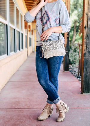 Small Grey Crossbody with Paisley Print and Cowhide, with Wristlet Strap, on Blonde Model, Taken Outside in Natural Light