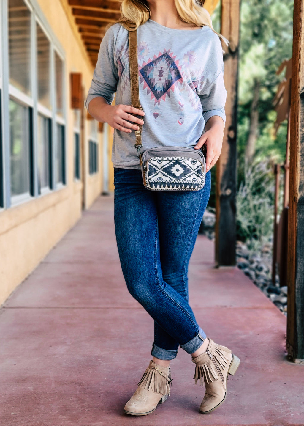 Small Grey Canvas Crossbody with Brown Leather Crossbody Strap and Dark Grey/Blue Aztec Print on Blonde Model Taken Outside in Natural Light