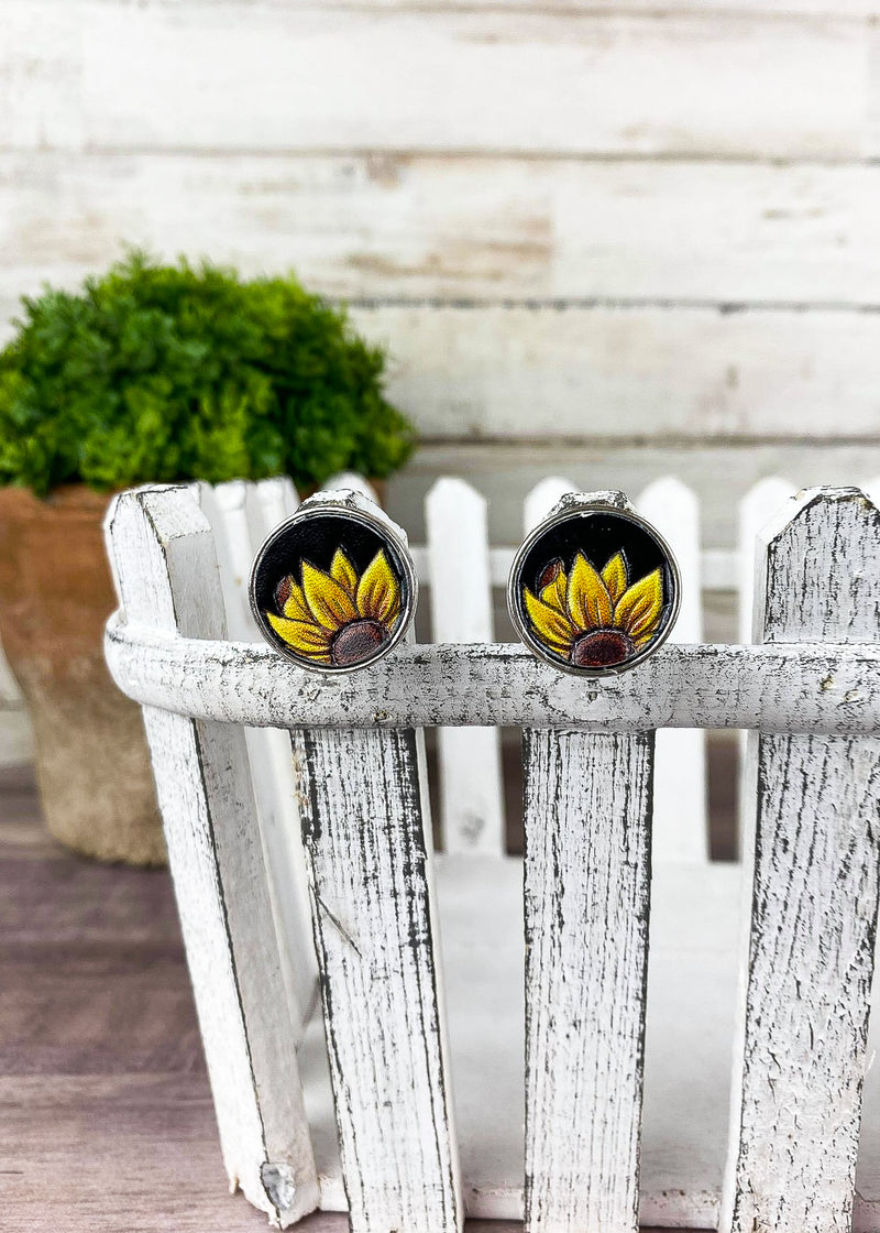 Small round stud leather post earrings with sunflower. on small white fence and plant décor