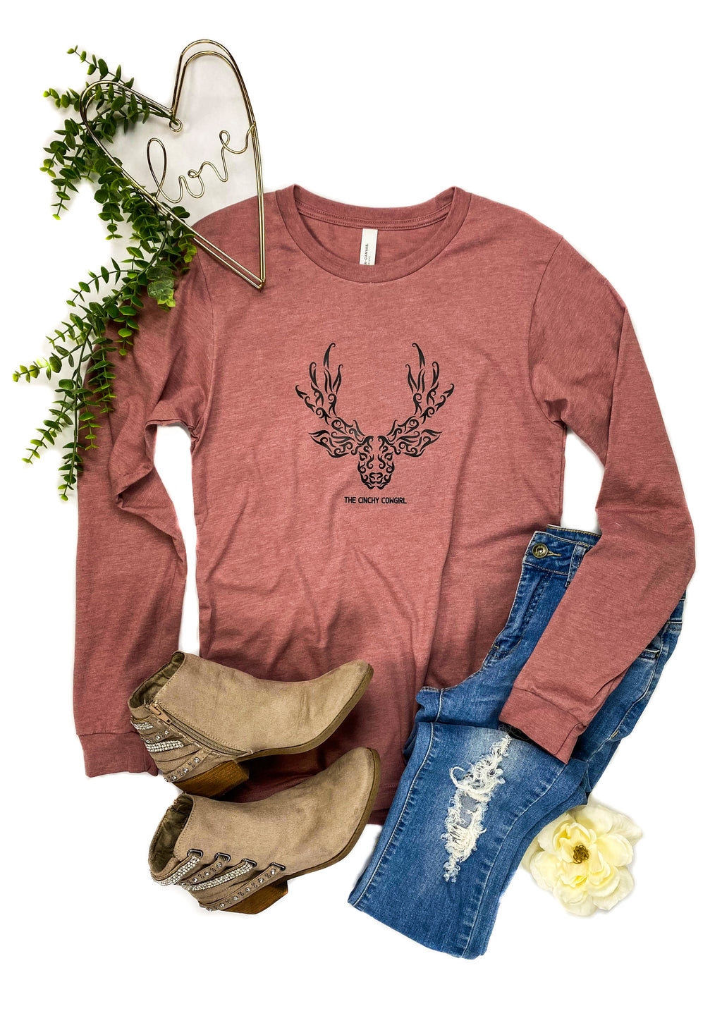 "Mauve Long Sleeve Tee Shirt with Deer Head and 'The Cinchy Cowgirl"" in Black Ink  in the Center of the Tee, Laid Flat on White Surface with Denim Jeans, Taupe Short Boots and Floral Accents"