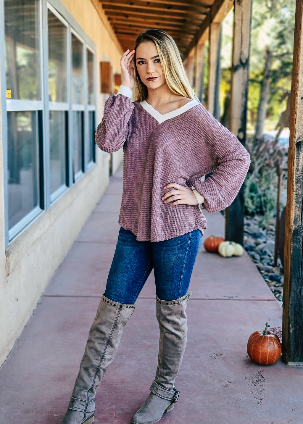 Mauve Waffle V Neck Long Sleeve Top with Ivory Trim Around the Neck and Arms, on Blonde Model With Denim Jeans and Knee High Boots, Taken Outside in Natural Light
