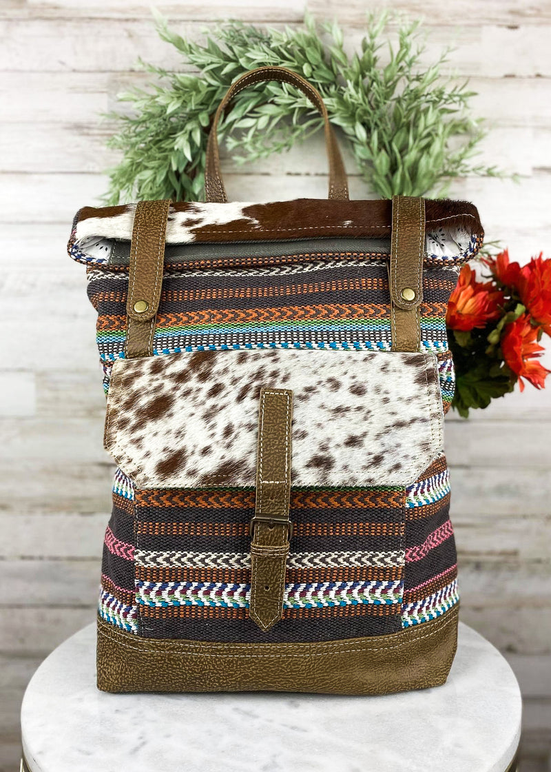 Large backpack with multicolor pattern and brown and white cowhide with front snap button pocket and flap over snap button top closure, with solid grey back and back zipper pocket, taken inside on white table with floral décor