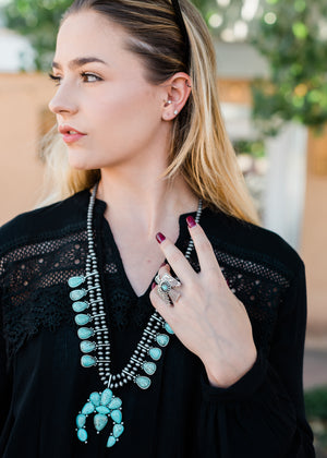 traditional silver Thunderbird ring with small faux Turquoise oval in the middle and aztec inspired etchings on blonde model wearing a black shirt and turquoise squash blossom