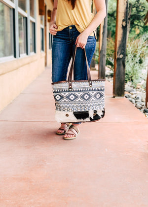 Brown Leather and Grey, Dark Blue and White Aztec Design with White and Black Cowhide Tote Handbag on Brunette Model