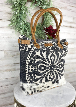 Large tote handbag with navy/dark grey canvas and rug material, and white printed paisley design and black and white cowhide at the bottom. brown leather accents and 2 handle straps, with outside back zipper pocket and 3 inside pockets, taken inside on white table with floral décor