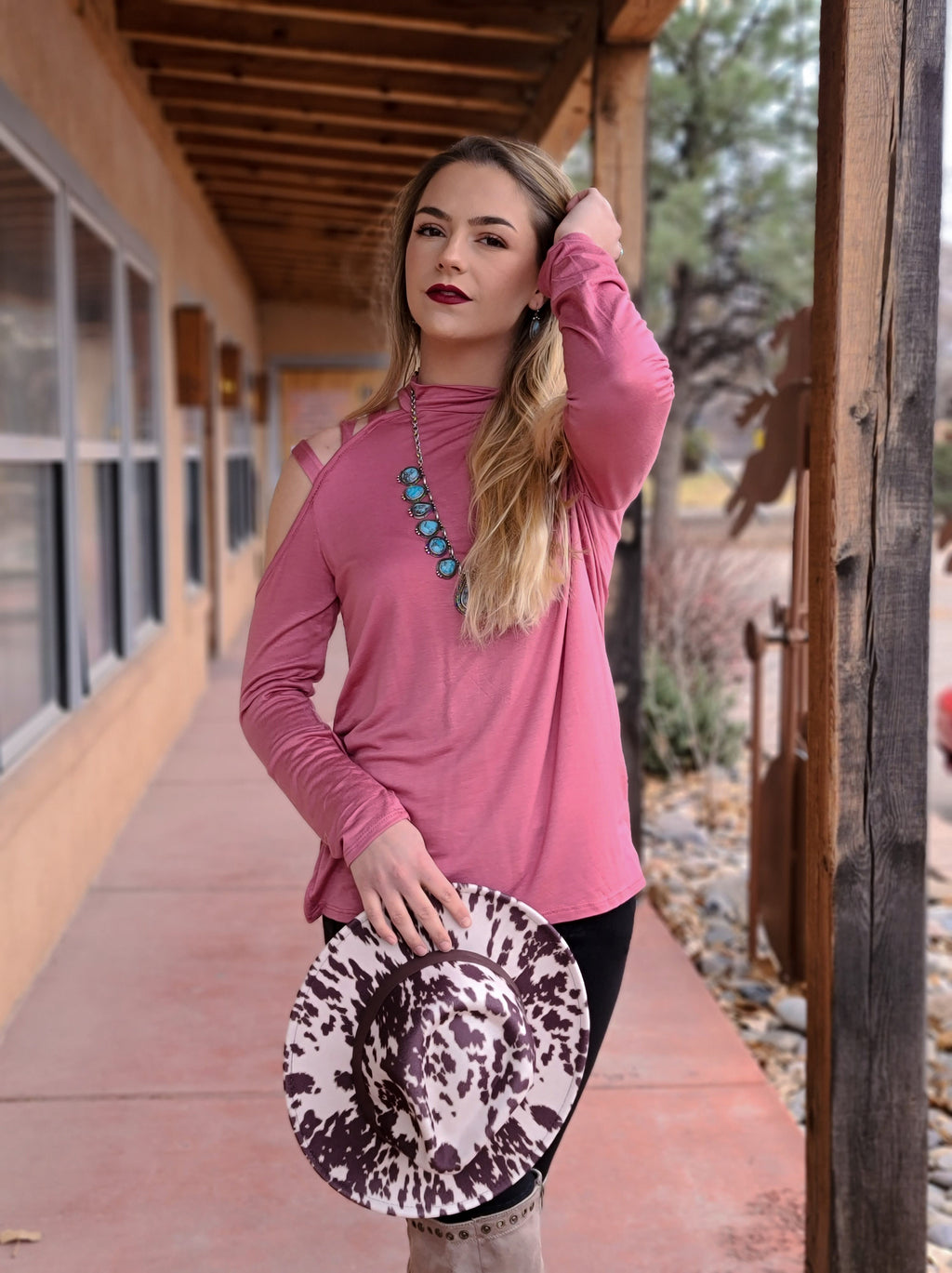 Pink long sleeve top with one arm cold shoulder and ladder detail, on blonde model taken outside