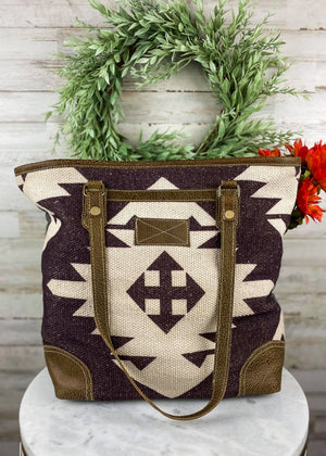 Tote handbag with plum and beige aztec print on front body and solid grey with a zipper pocket on back of bag, with brown leather accents and 2 brown leather shoulder straps, taken inside on white table with floral décor