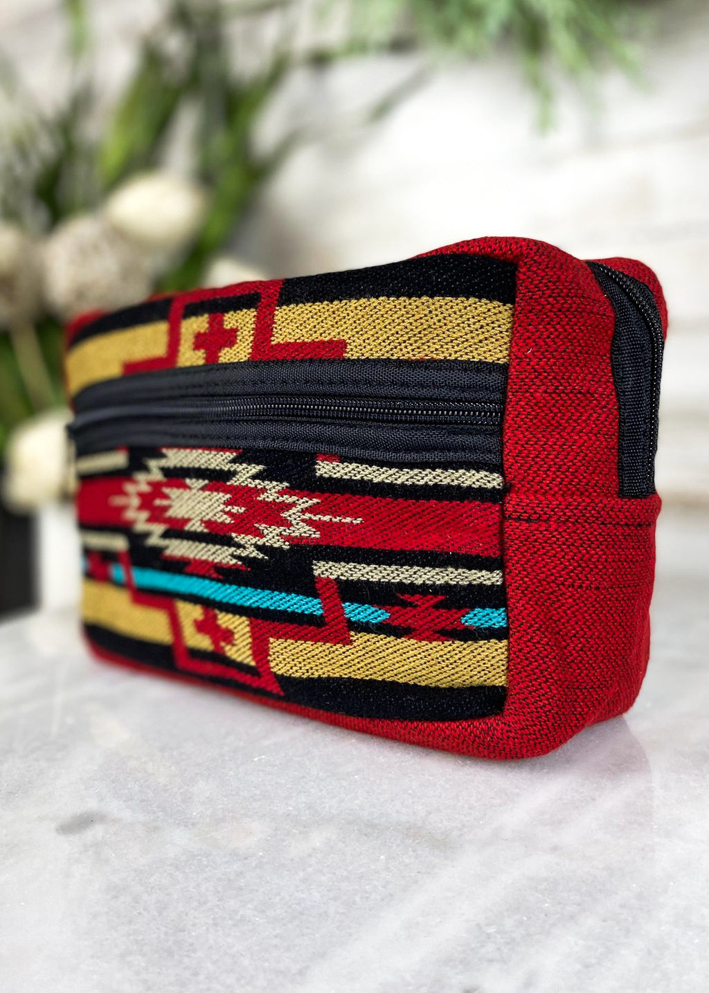 Red and multicolored aztec southwestern cosmetic bag with front zipper pocket, taken inside on white table with floral décor