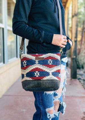 Medium sized crossbody with red, blue, and ivory Aztec print and grey cowhide, brown leather crossbody strap, taken outside on model wearing distressed denim jeans and black hoodie