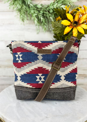 Medium sized crossbody with red, blue, and ivory Aztec print and grey cowhide, brown leather crossbody strap, taken inside on white table with studio lights and green and floral décor