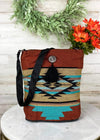 Medium sized rust and turquoise shoulder bag with silver concho detail and small black fringe, with aztec print, taken inside on white table with floral décor