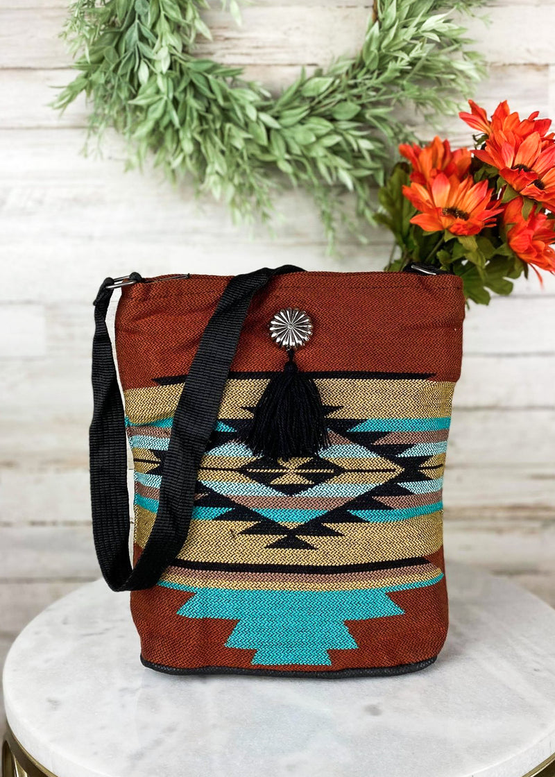 Medium sized rust and turquoise shoulder bag with silver concho detail and small black fringe, with aztec print, taken inside on model