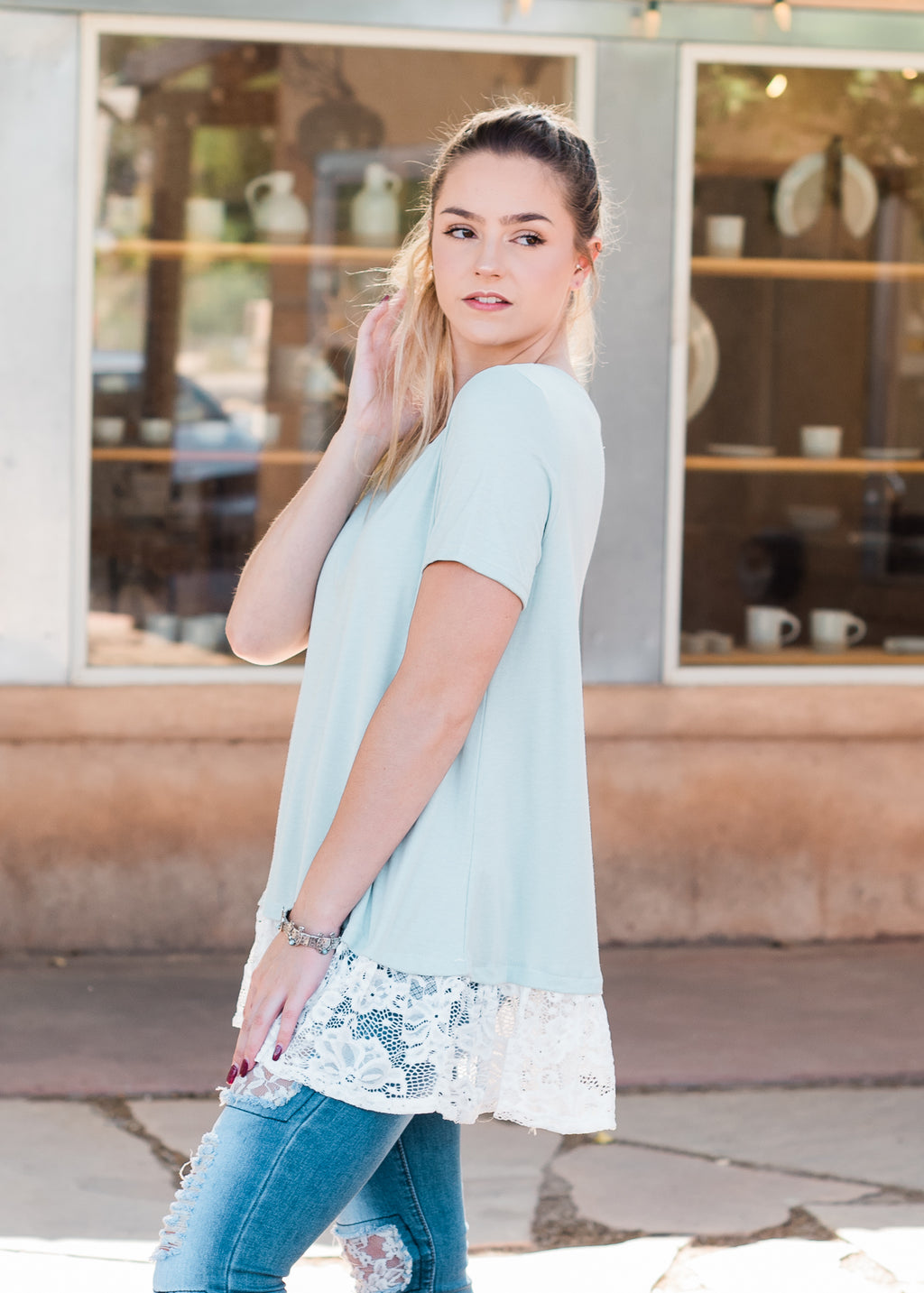 very light sage color short sleeve top with white lace along the bottom and faux button-up details on the back on a blonde model wearing jeans