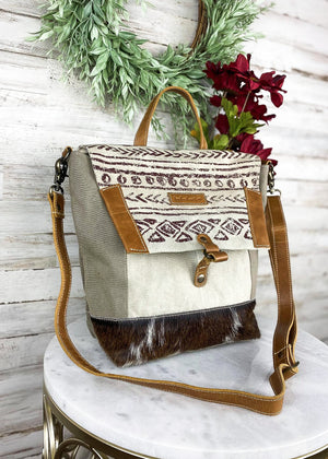 Medium crossbody with tan and grey/green canvas with abraded print on flap over closure and brown cowhide at the bottom, with top handle and adjustable crossbody strap, brown leather accents, and 3 inside pockets, taken inside on white table with floral décor