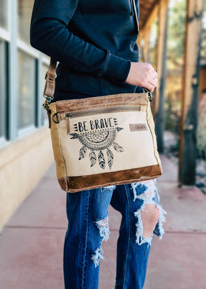 "Tan Crossbody / Shoulder Bag with ""Be Brave"" and Dreamcatcher Print with Brown Leather strap, taken outside on model wearing distressed denim jeans and a black hoodie"
