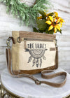 "Tan Crossbody / Shoulder Bag with ""Be Brave"" and Dreamcatcher Print with Brown Leather strap, taken inside on white table with green and floral plant décor"