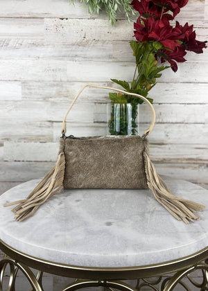 Small tan colored clutch handbag with crossbody strap with tan cowhide over the whole bag, and tan colored fringe in the front, taken inside on white table with floral décor