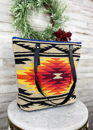 Large Tan and multicolor tote handbag with Aztec print on the front and two black shoulder straps, taken inside on white table with floral décor