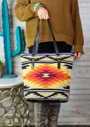 Large Tan and multicolor tote handbag with Aztec print on the front and two black shoulder straps, taken inside on model