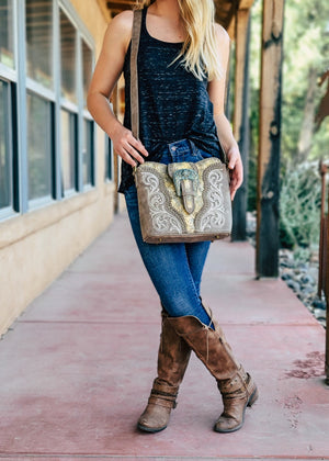 Tan Patina Buckle Concealed Carry Crossbody Handbag on Blonde Model Taken Outside