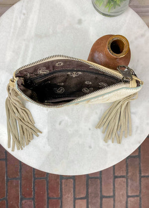 Inside of Small White Cowhide Crossbody/Wristlet with Tan Speckled Spots and Tan Fringe on the Sides, Taken Inside on White Table With Studio Lights and Floral Décor