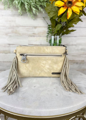 Back of Small White Cowhide Crossbody/Wristlet with Tan Speckled Spots and Tan Fringe on the Sides and Back Outside Zipper Pocket, Taken Inside on White Table With Studio Lights and Floral Décor