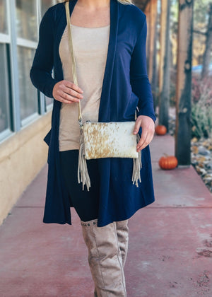 Small White Cowhide Crossbody/Wristlet with Tan Speckled Spots and Tan Fringe on the Sides, Taken Outside on Blonde Model Wearing a Navy Cardigan and Taupe Knee High Boots