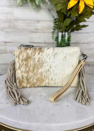 Small White Cowhide Crossbody/Wristlet with Tan Speckled Spots and Tan Fringe on the Sides, Taken Inside on White Table With Studio Lights and Floral Décor