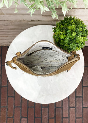 Inside of Medium Crossbody with Tan and Black Vintage Looking Floral Detail and Brown Leather Accents, Wristlet and Crossbody Strap, Taken Inside on White Table With Studio Lights and Green Plant Accents