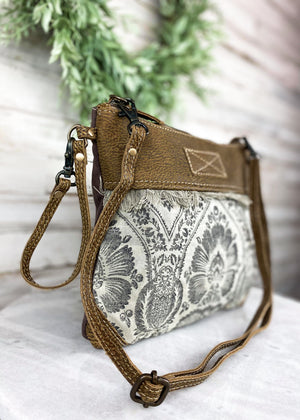 Medium Crossbody with Tan and Black Vintage Looking Floral Detail and Brown Leather Accents, Wristlet and Crossbody Strap, Taken Inside on White Table With Studio Lights and Green Plant Accents