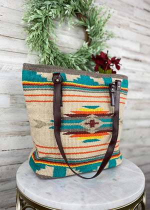 Large Tan Tote Handbag with Turquoise, Red, and Yellow Aztec Print on the front and two brown shoulder straps, taken inside on white table with floral décor