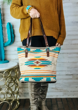 Large Tan Tote Handbag with Turquoise, Red, and Yellow Aztec Print on the front and two brown shoulder straps, taken inside on model