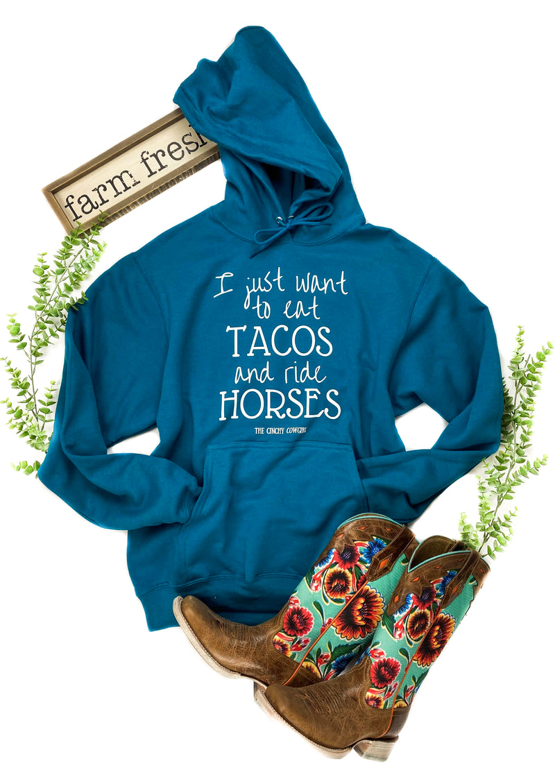 "Teal Hoodie with ""I Just Want to Eat Tacos and ride Horses"" Laid Flat on White Surface with Floral Décor"