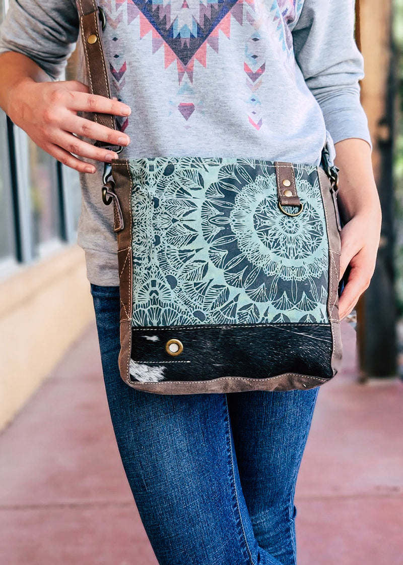 Brown Canvas Medium Crossbody with Black and White Cowhide and Teal Abstract Floral Print on Blonde Model Taken Outside in Natural Light