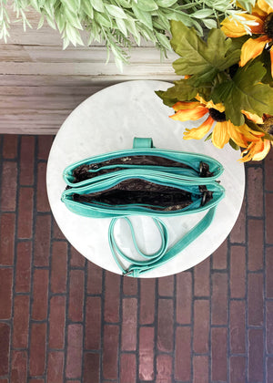 Inside View of Medium Turquoise Colored Crossbody with Embossed Floral Print with 2 Zipper Pockets and a Middle Hidden Pocket