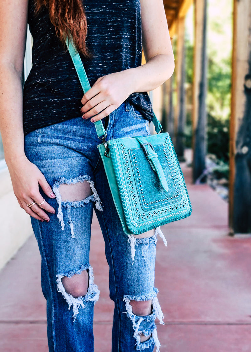 Medium Turquoise Colored Crossbody with Embossed Floral Print on Brunette Model